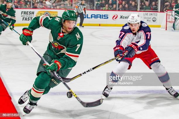 Matt Cullen of the Minnesota Wild skates with the puck while Josh Anderson of the Columbus Blue Jackets defends during the game at the Xcel Energy...