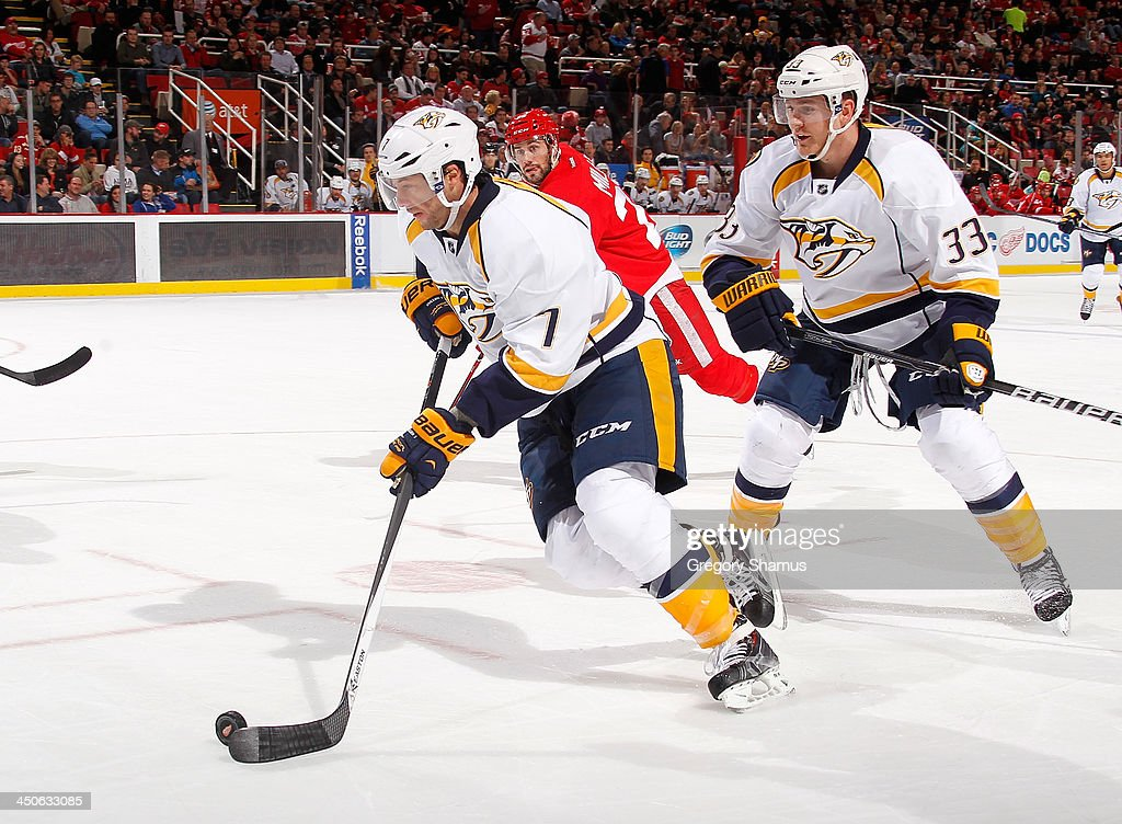 Matt Cullen #7 of the Nashville Predators skates the puck in front of teammate Colin Wilson #33 and Drew Miller #20 of the Detroit Red Wings at Joe Louis Arena on November 19, 2013 in Detroit, Michigan.