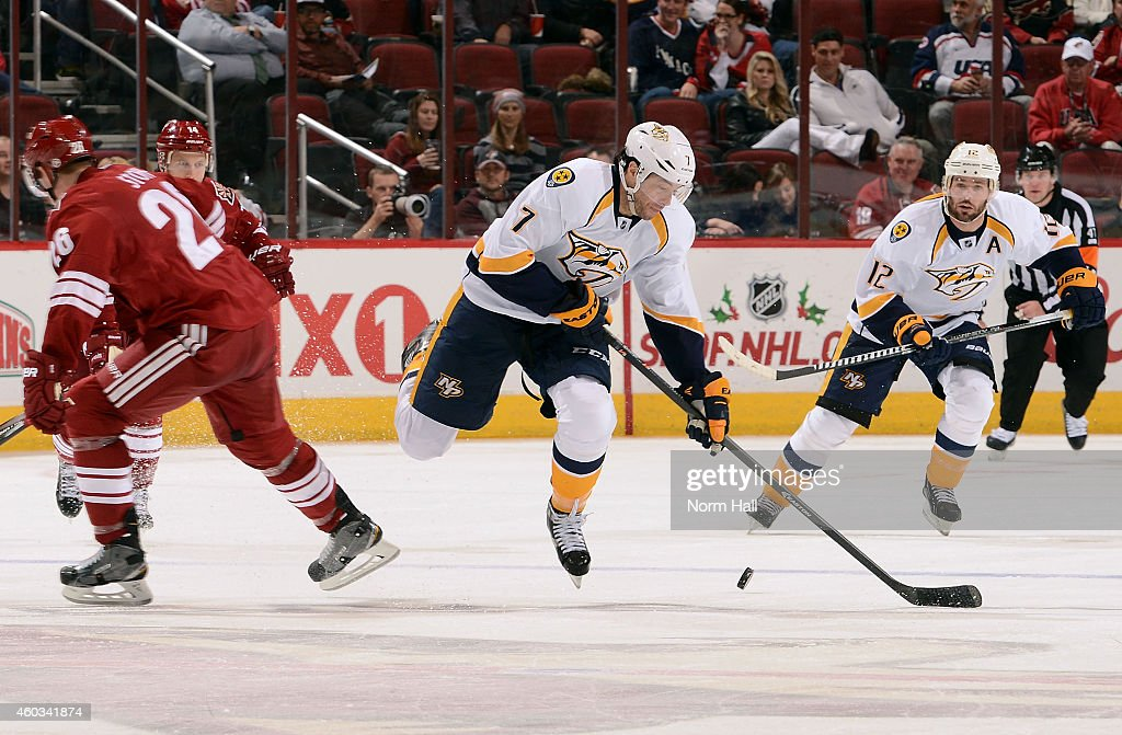 Matt Cullen #7 of the Nashville Predators skates with the puck around Michael Stone #26 of the Arizona Coyotes during the third period at Gila River Arena on December 11, 2014 in Glendale, Arizona.
