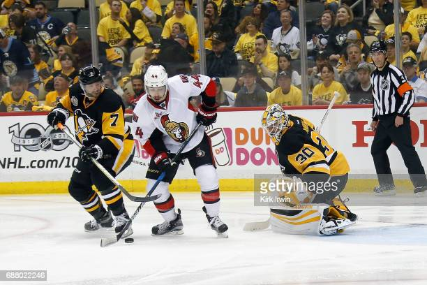 Matt Cullen of the Pittsburgh Penguins and JeanGabriel Pageau of the Ottawa Senators battle for control of the puck in front of Matt Murray of the...