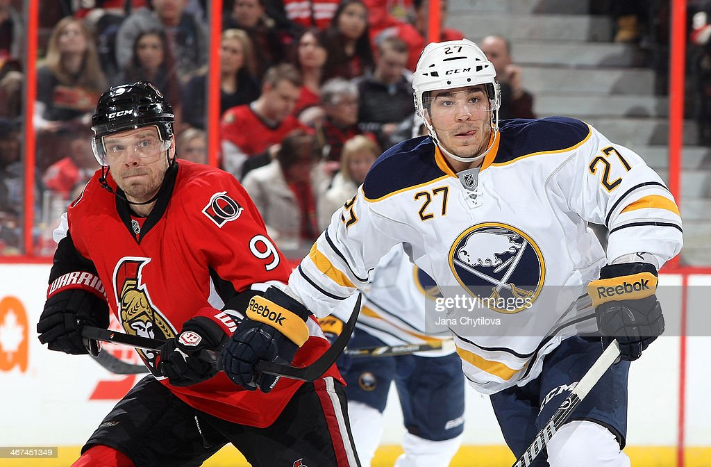 Matt D'Agostini #27 of the Buffalo Sabres playing in his 300th career NHL game holds the stick of Milan Michalek #9 of the Ottawa Senators during an NHL game at Canadian Tire Centre on February 6, 2014 in Ottawa, Ontario, Canada.