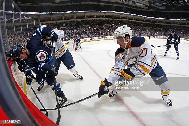 Matt D'Agostini of the Buffalo Sabres tries to win the puck away from Zach Bogosian of the Winnipeg Jets along the boards during first period action...