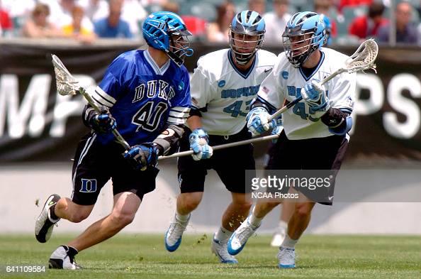 Matt Danowski of Duke tries to work around Chris Watson and Matt Feild of Johns Hopkins during the Division I Men's Lacrosse Championship help at...