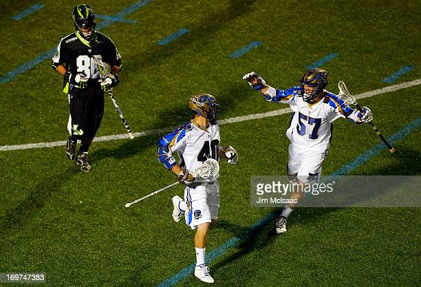 Matt Danowski of the Charlotte Hounds celebrates his second goal with teammate Peet Poillon as Kevin Unterstein of the New York Lizards looks onb...