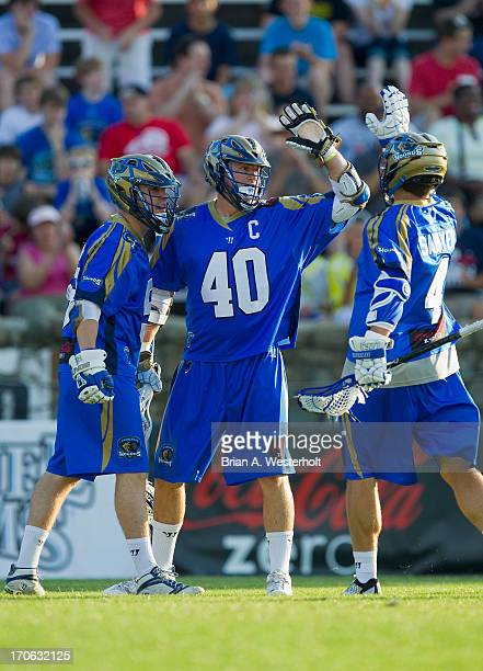 Matt Danowski of the Charlotte Hounds celebrates with teammates Mike Sawyer and Peet Poillon after scoring a goal against the Boston Cannons at...