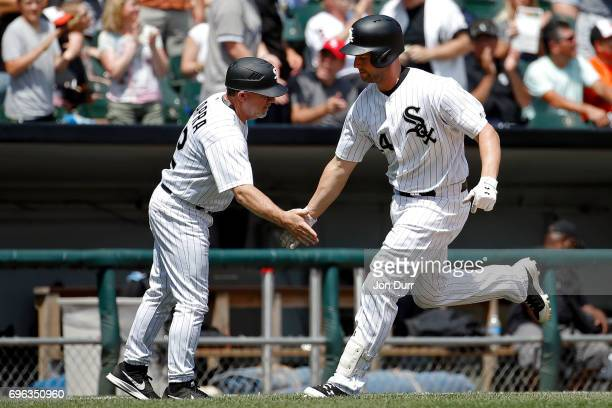Matt Davidson of the Chicago White Sox is congratulated by third base coach Nick Capra after hitting a home run against the Baltimore Orioles during...