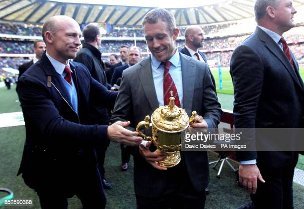 Matt Dawson hands Jonny Wilkinson the World Cup on their lap of honour to mark the 10 year anniversary of winning the World Cup at half time during...
