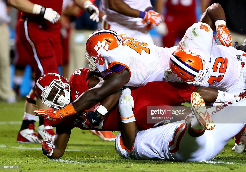 Matt Dayes #21 of the North Carolina State Wolfpack is hit hard by the Clemson Tigers during their game at Carter-Finley Stadium on September 19, 2013 in Raleigh, North Carolina.