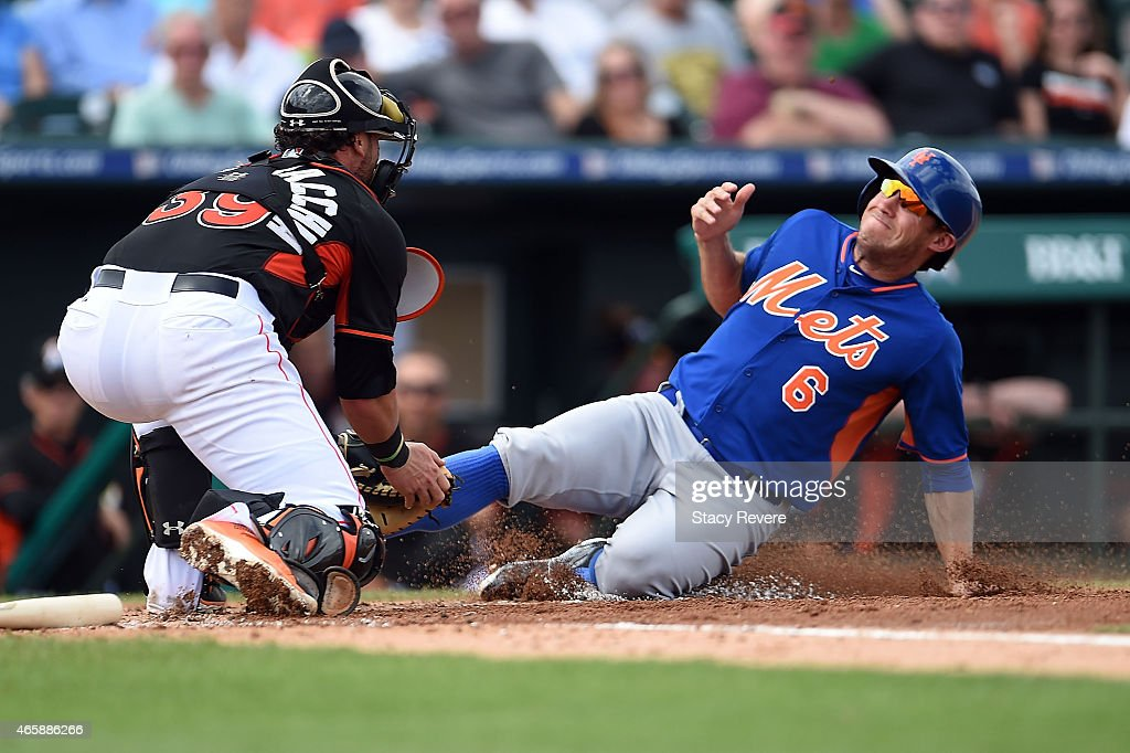 Matt den Dekker of the New York Mets is tagged out at home plate by Jarrod Saltalamacchia of the Miami Marlins during a spring training game at Roger...