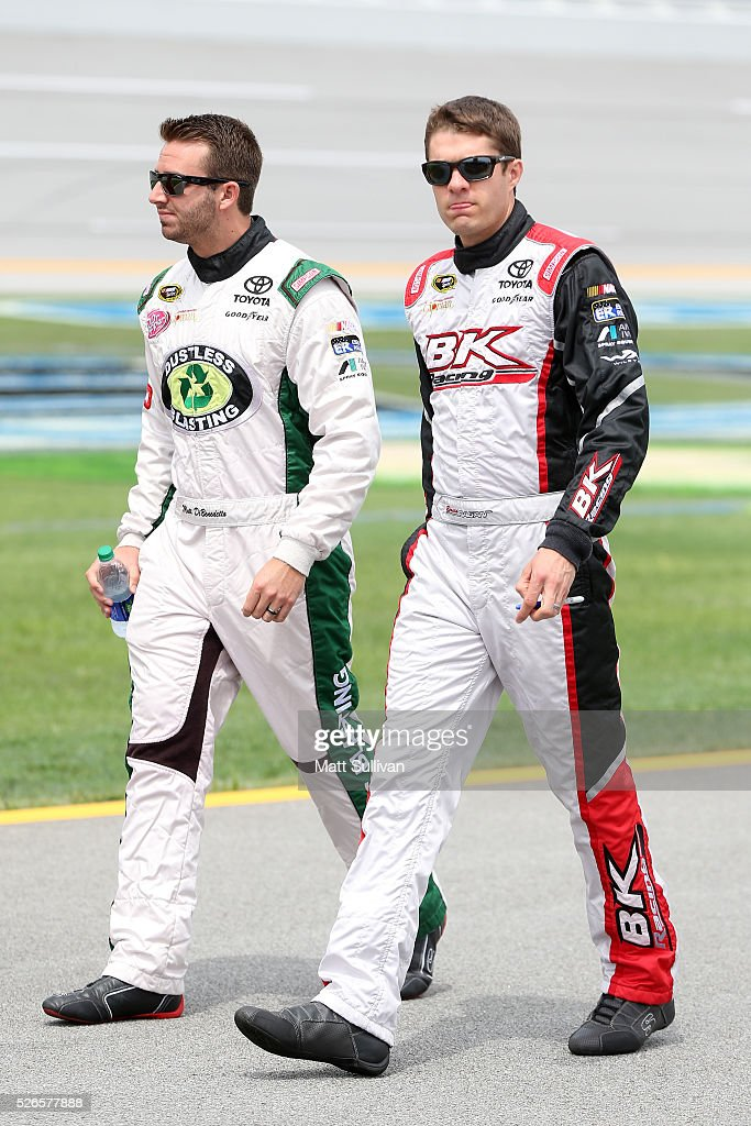 Matt DiBenedetto, driver of the #83 Dustless Blasting Toyota, and David Ragan, driver of the #23 Schluter Systems Toyota, walk on the grid during qualifying for the NASCAR Sprint Cup Series GEICO 500 at Talladega Superspeedway on April 30, 2016 in Talladega, Alabama.