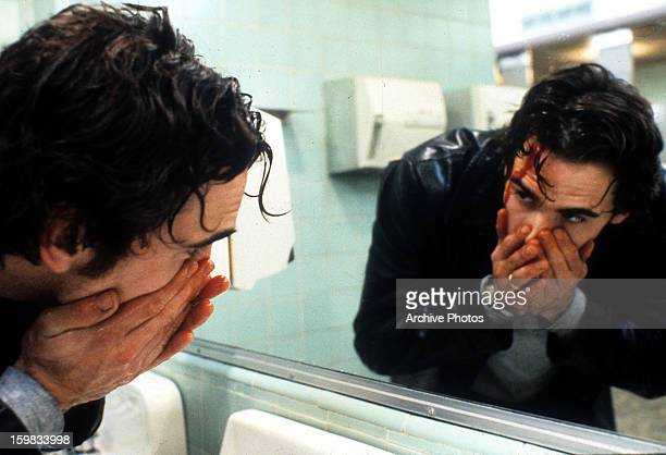 Matt Dillon looking at blood streaming down his face in mirror in a scene from the film 'Drugstore Cowboy' 1989