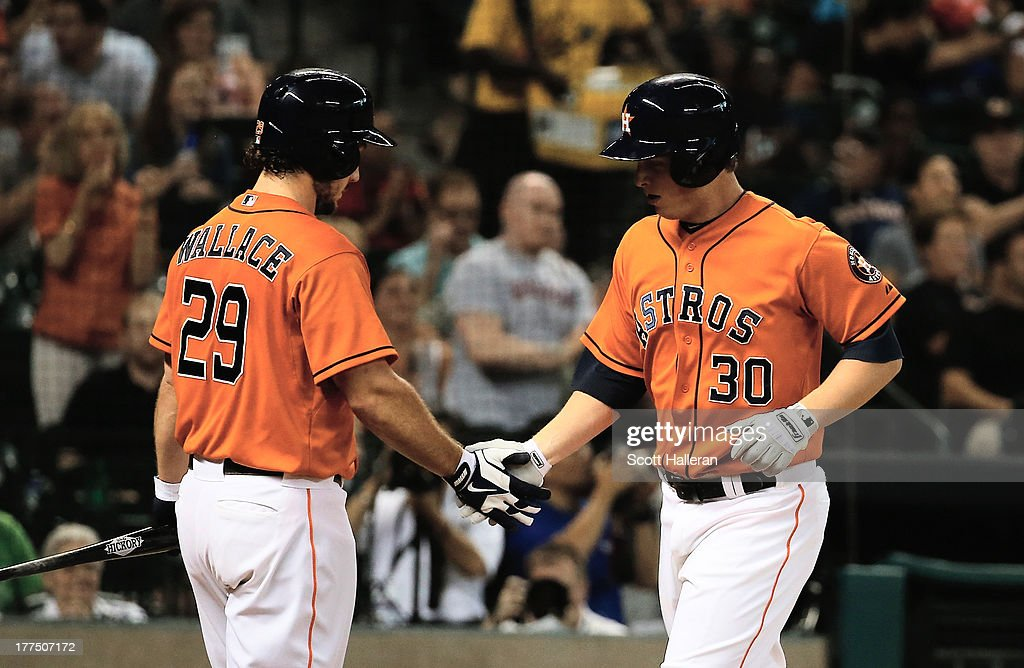 Matt Dominguez #30 and Brett Wallace #29 of the Houston Astros celebrate after Dominguez hit a solo home run in the second inning against the Toronto Blue Jays at Minute Maid Park on August 23, 2013 in Houston, Texas.