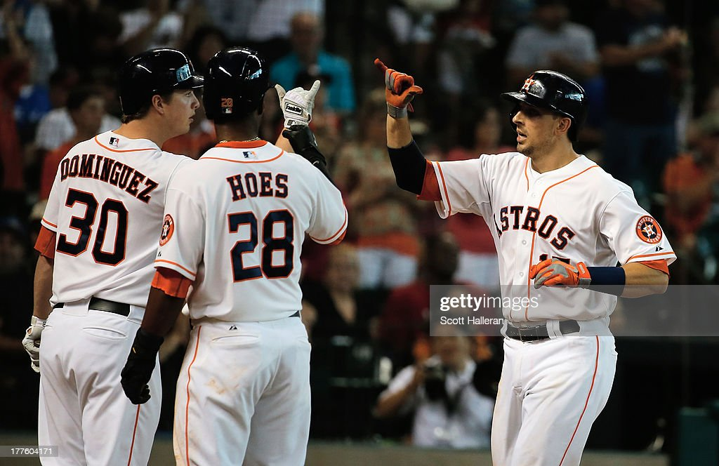 Matt Dominguez #30 and L.J. Hoes #28 of the Houston Astros greet Jason Castro #15 at home plate after Castro hit a two run home run in the third inning against the Toronto Blue Jays at Minute Maid Park on August 24, 2013 in Houston, Texas.