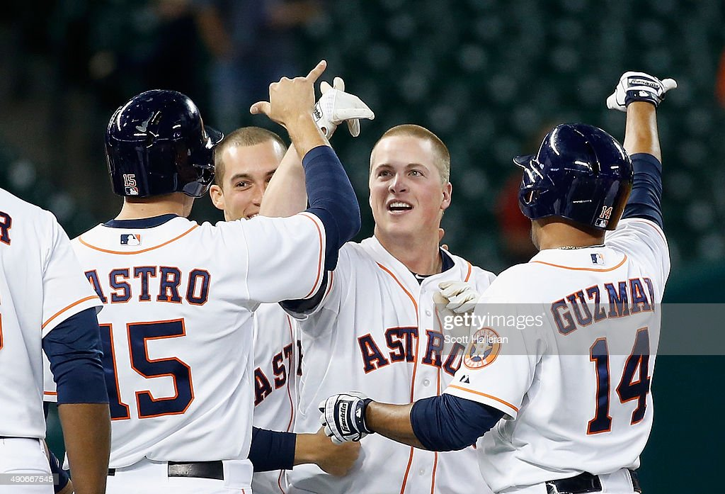 Matt Dominguez #30 (C) of the Houston Astros celebrates with his teammates after he drove in the winning run with an RBI single in the ninth inning to defeat the Texas Rangers 5-4 at Minute Maid Park on May 14, 2014 in Houston, Texas.