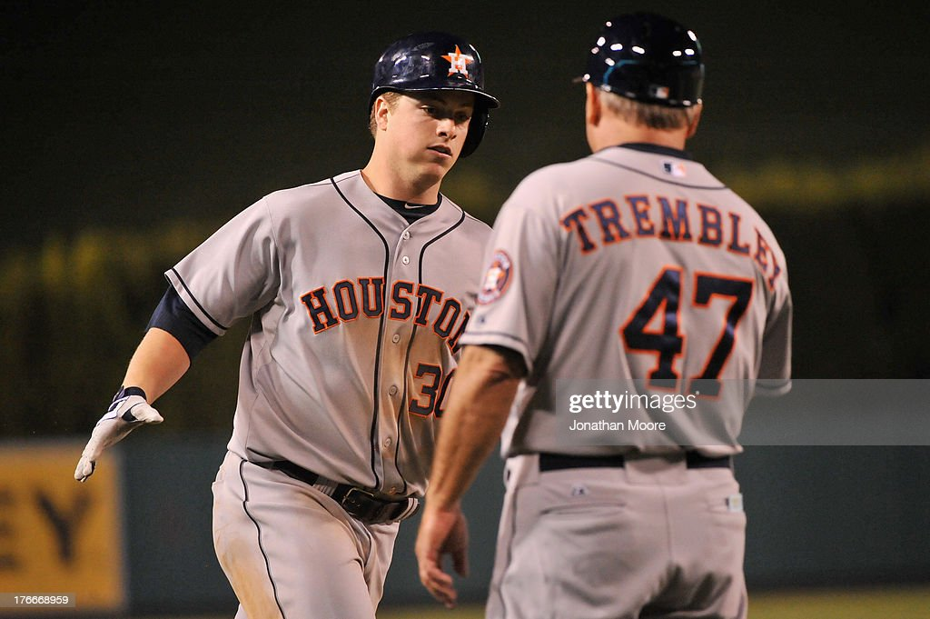 Matt Dominguez #30 of the Houston Astros celebrates with Third Base Coach Dave Trembley #47 after hitting a home run in the eighth inning during a game against the Los Angeles Angels of Anaheim at Angel Stadium of Anaheim on August 16, 2013 in Anaheim, California.