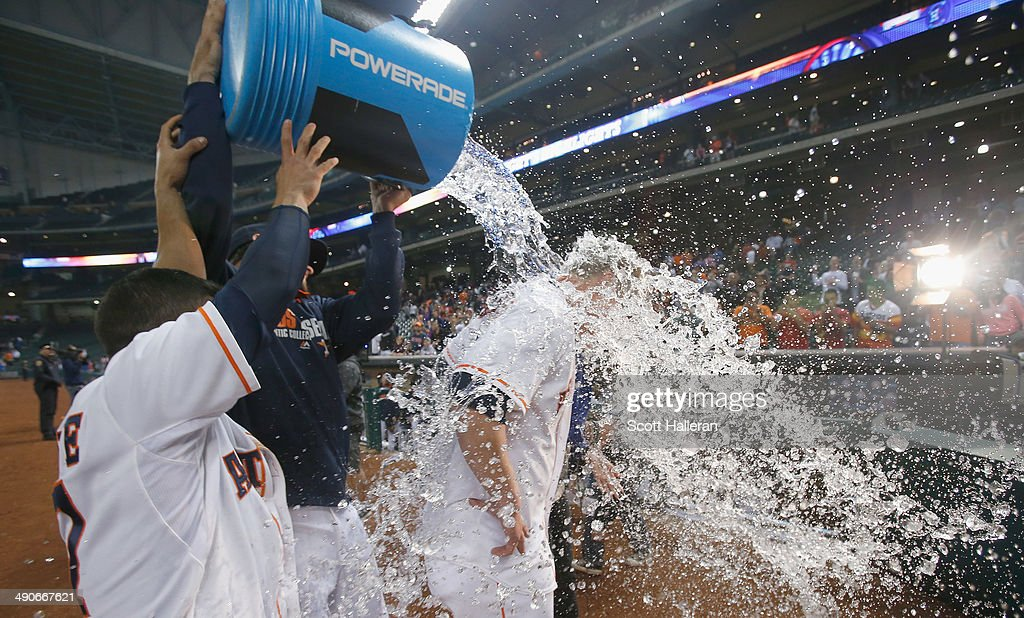 Matt Dominguez #30 (C) of the Houston Astros gets soaked with water by Jose Altuve #27 after he drove in the winning run with an RBI single in the ninth inning to defeat the Texas Rangers 5-4 at Minute Maid Park on May 14, 2014 in Houston, Texas.