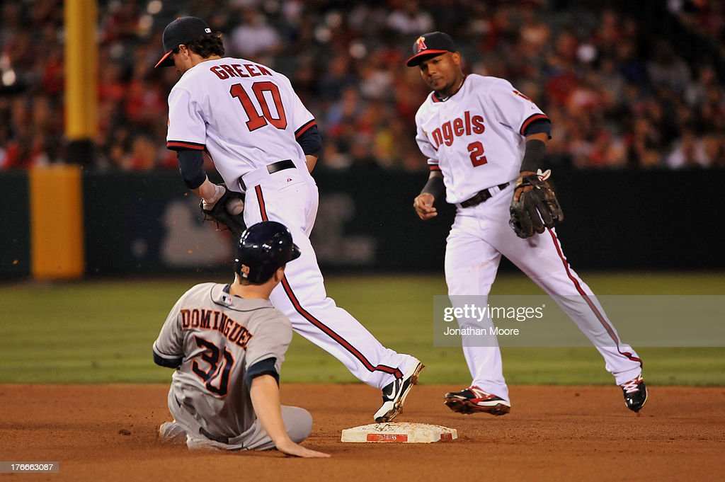 Matt Dominguez #30 of the Houston Astros is forced out at second base by Grant Green #10 of the Los Angeles Angels of Anaheim as Erick Aybar #2 looks on in the fourth inning during a game at Angel Stadium of Anaheim on August 16, 2013 in Anaheim, California.