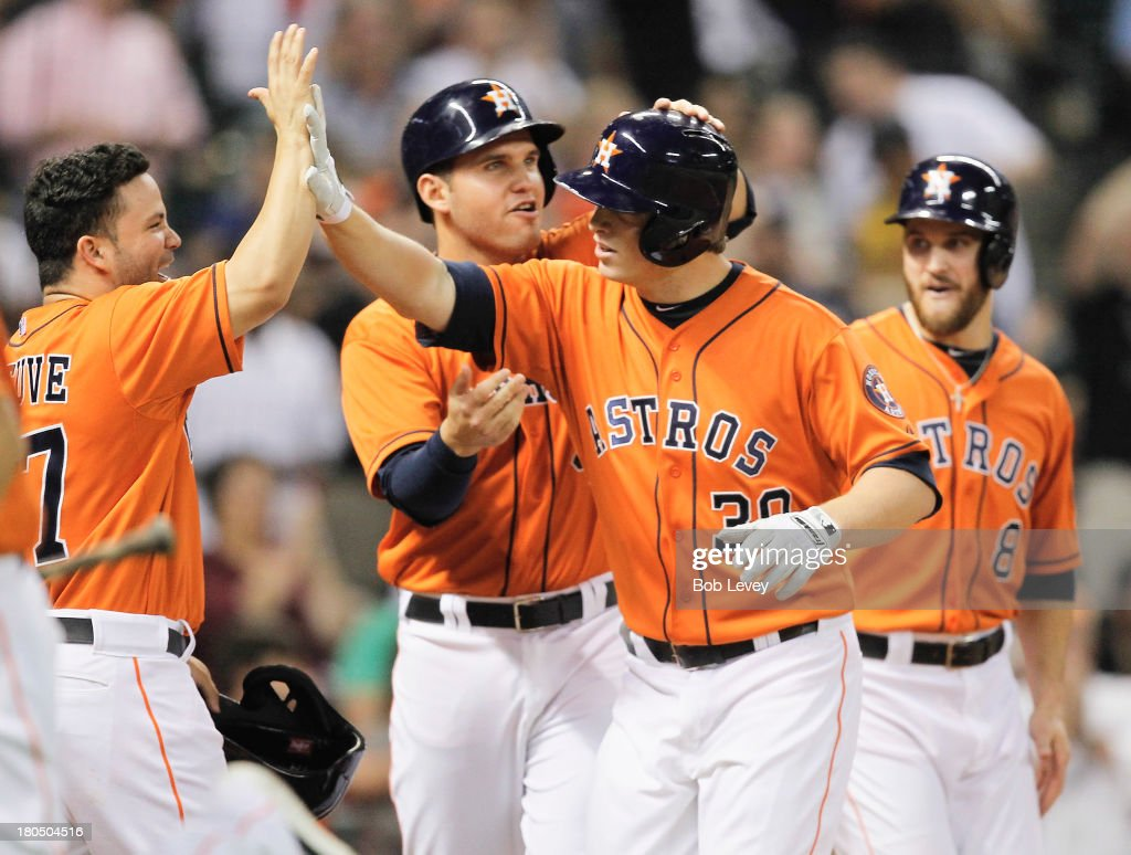 Matt Dominguez #30 of the Houston Astros receives high fives from Jose Altuve #27, Trevor Crowe #8 and Brandon Laird #4 after hitting a grand slam in the fifth inning against the Los Angeles Angels of Anaheim at Minute Maid Park on September 13, 2013 in Houston, Texas.