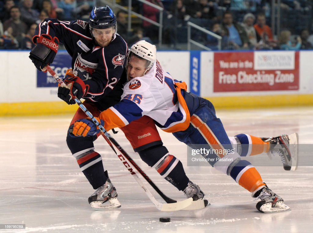 Matt Donovan #46 of the Bridgeport Sound Tigers holds Ryan Russell #20 of the Springfield Falcons as they skate during an American Hockey League game on January 20, 2013 at the Webster Bank Arena at Harbor Yard in Bridgeport, Connecticut.