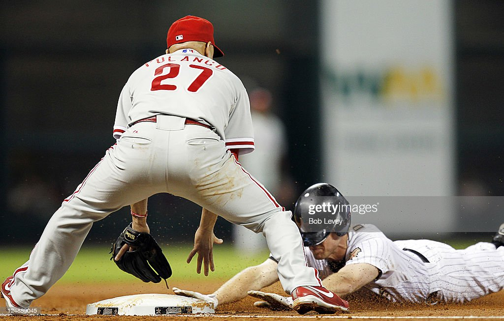 Matt Downs #16 of the Houston Astros slides safely into third base as third baseman Placido Polanco #27 of the Philadelphia Phillies awaits the ball after it got past center fielder John Mayberry in the third inning at Minute Maid Park on September 13, 2011 in Houston, Texas.