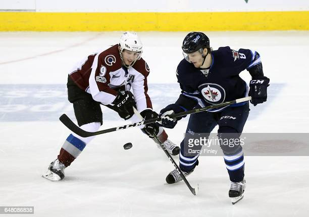 Matt Duchene of the Colorado Avalanche and Jacob Trouba of the Winnipeg Jets battle for the puck during second period action at the MTS Centre on...
