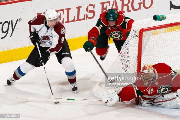 Matt Duchene of the Colorado Avalanche attempts a wrap around on Anton Khudobin of the Minnesota Wild while Greg Zanon defends during the game at...
