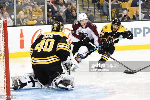 Matt Duchene of the Colorado Avalanche fights for the puck against Tuukka Rask and Kevan Miller of the Boston Bruins at the TD Garden on October 9...
