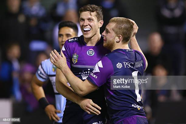 Matt Duffie and Cameron Munster of the Storm celebrate Cameron Munster scoring a try during the round 23 NRL match between the Cronulla Sharks and...