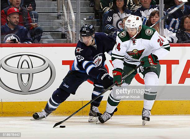 Matt Dumba of the Minnesota Wild plays the puck away from a defending Mark Scheifele of the Winnipeg Jets during second period action at the MTS...