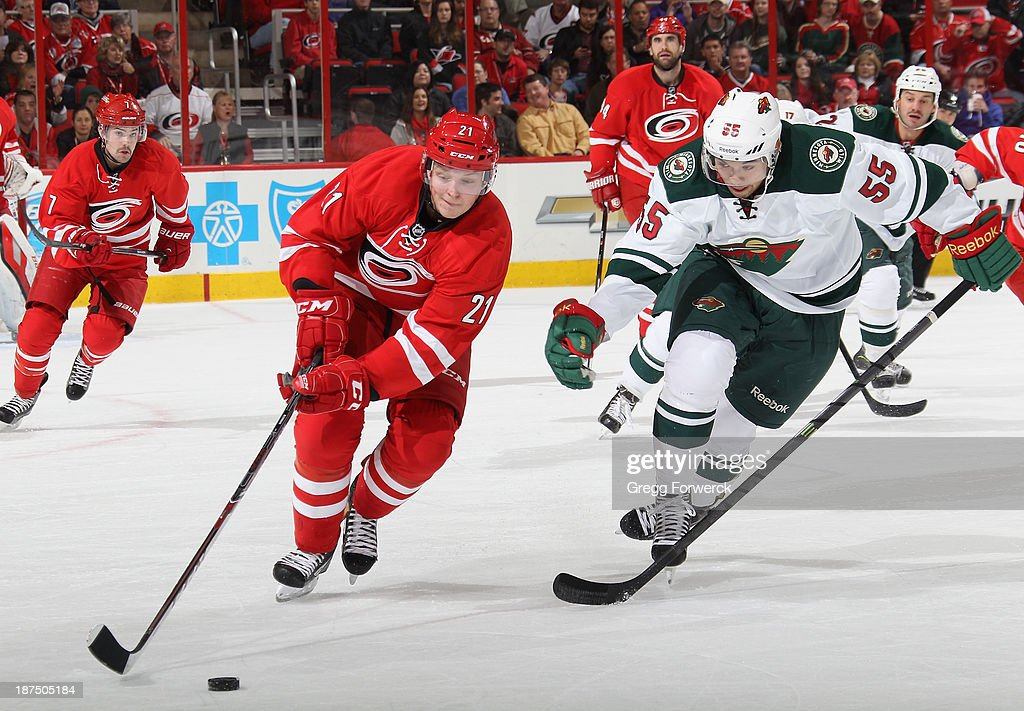 Matt Dumba #55 of the Minnesota Wild pursues Drayson Bowman #21 of the Carolina Hurricanes as he carries the puck during their NHL game at PNC Arena on November 9, 2013 in Raleigh, North Carolina.