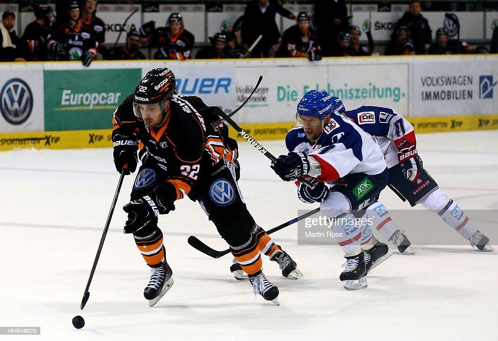 Matt Dzieduszycki of Wolfsburg and Brandon Yip of Mannheim battle for the puck during the DEL match between Grizzly Adams Wolfsburg and Adler...