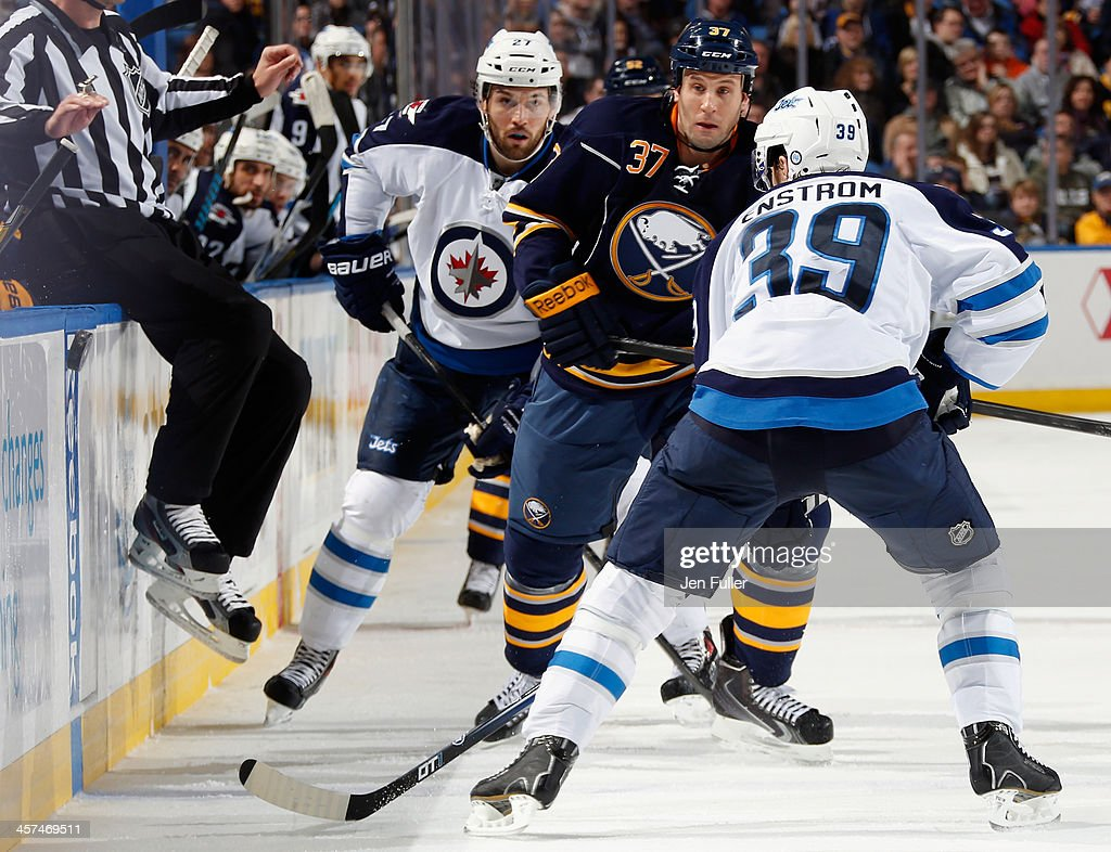 Matt Ellis #37 of the Buffalo Sabres tips the puck along the boards while skating against Tobias Enstrom #39 and Eric Tangradi #27 of the Winnipeg Jets at First Niagara Center on December 17, 2013 in Buffalo, New York. Buffalo defeated Winnipeg 4-2.