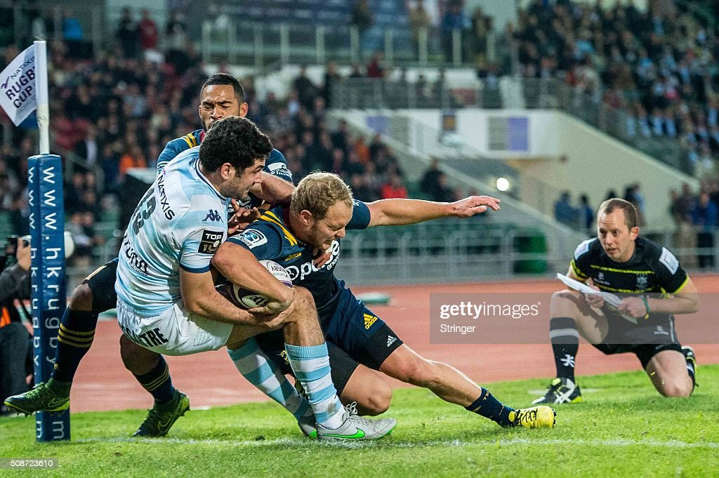 Matt Faddes (C) of Pulse Energy Highlanders moves the ball up against Racing 92 during the Natixis Rugby Cup on February 6, 2016 at the Sui Sai Wan stadium in Chai Wan, Hong Kong.