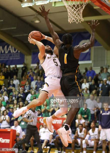 Matt Farrell of the Notre Dame Fighting Irish makes contact with Zach Brown of the Wichita State Shockers as he shoots the ball during the second...