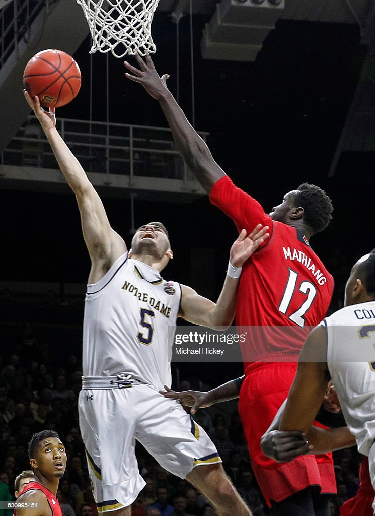 Matt Farrell #5 of the Notre Dame Fighting Irish shoots the ball against Mangok Mathiang #12 of the Louisville Cardinals at Purcell Pavilion on January 4, 2017 in South Bend, Indiana.