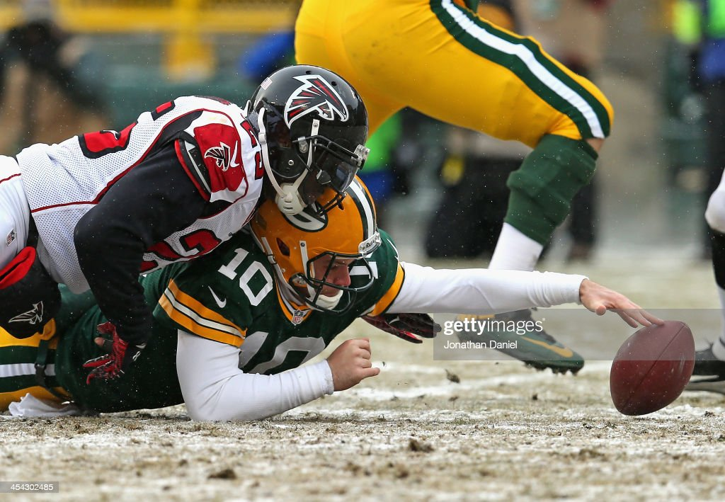 Matt Flynn #10 of the Green Bay Packers reaches for the ball after fumbling on a hit by William Moore #25 of the Atlanta Falcons at Lambeau Field on December 8, 2013 in Green Bay, Wisconsin.