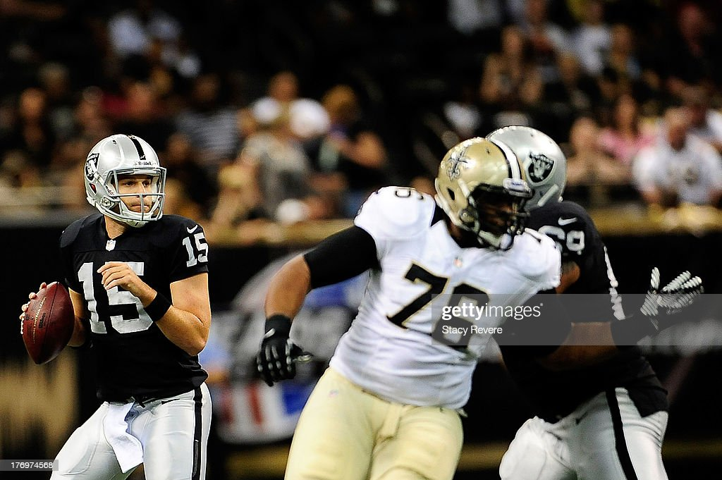 Matt Flynn #15 of the Oakland Raiders looks for an open receiver during a preseason game against the New Orleans Saints at the Mercedes-Benz Superdome on August 16, 2013 in New Orleans, Louisiana. The Saints won 28-20.