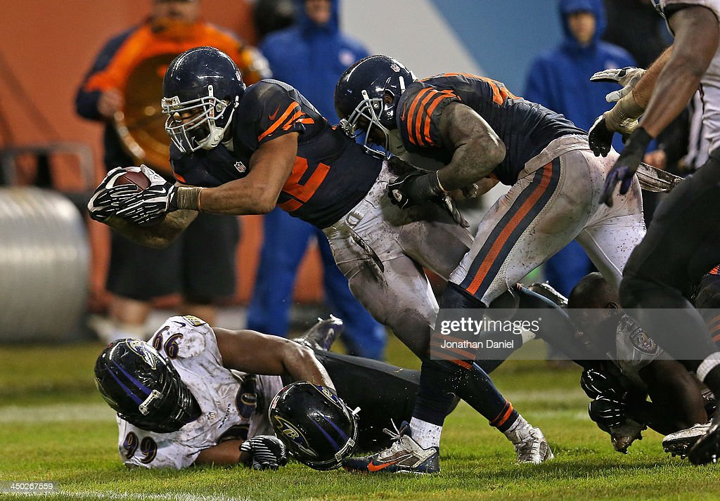 Matt Forte #22 of the Chicago Bears dives over Chris Canty #99 of the Baltimore Ravens to score a touchdown at Soldier Field on November 17, 2013 in Chicago, Illinois. The Bears defeated the Ravens 23-20 in overtime.