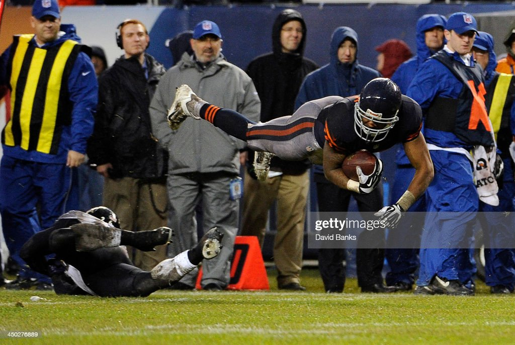 Matt Forte #22 of the Chicago Bears dives over Matt Elam #26 of the Baltimore Ravens during the fourth quarter on November 17, 2013 at Soldier Field in Chicago, Illinois. The Chicago Bears defeated the Baltimore Ravens 23-20 in overtime.