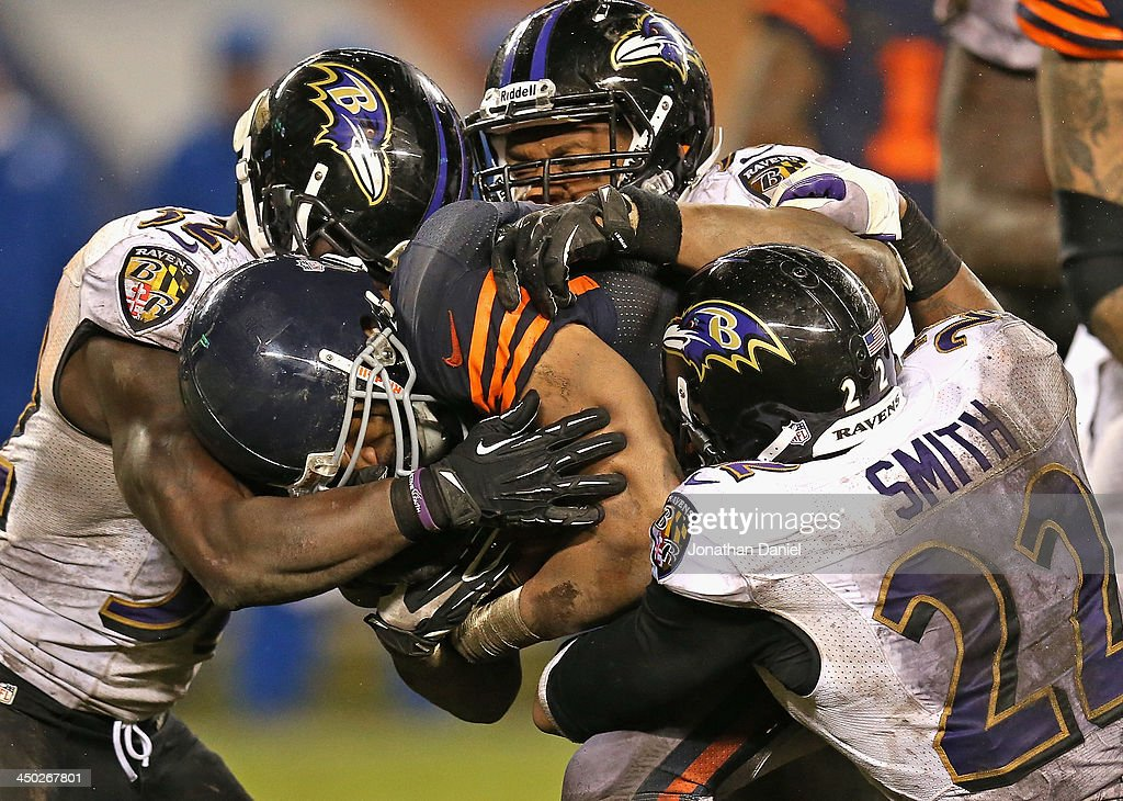 Matt Forte #22 of the Chicago Bears is hit by (L-R) James Ihedigbo #32, Daryl Smith #51 and Jimmy Smith #22 of the Baltimore Ravens at Soldier Field on November 17, 2013 in Chicago, Illinois. The Bears defeated the Ravcens 23-20 in overtime.