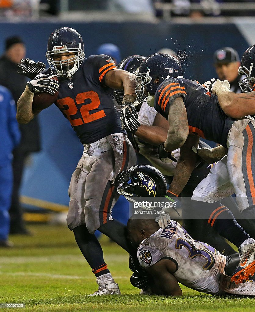 Matt Forte #22 of the Chicago Bears runs for a touchdown as James Ihedigbo #32 of the Baltimore Ravens looses his helmet trying to make the tackle at Soldier Field on November 17, 2013 in Chicago, Illinois. The Bears defeated the Ravens 23-20 in overtime.