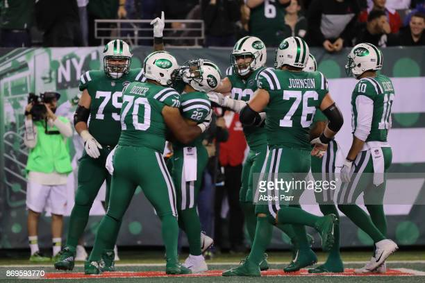 Matt Forte of the New York Jets is congratulated by teammates Dakota Dozier Wesley Johnson and Brent Qvale after Forte scored a touchdown during the...