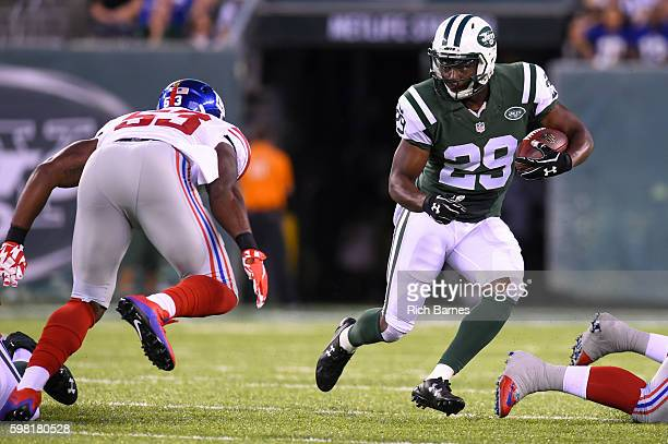Matt Forte of the New York Jets runs with the ball as Jasper Brinkley of the New York Giants defends during the first quarter at MetLife Stadium on...