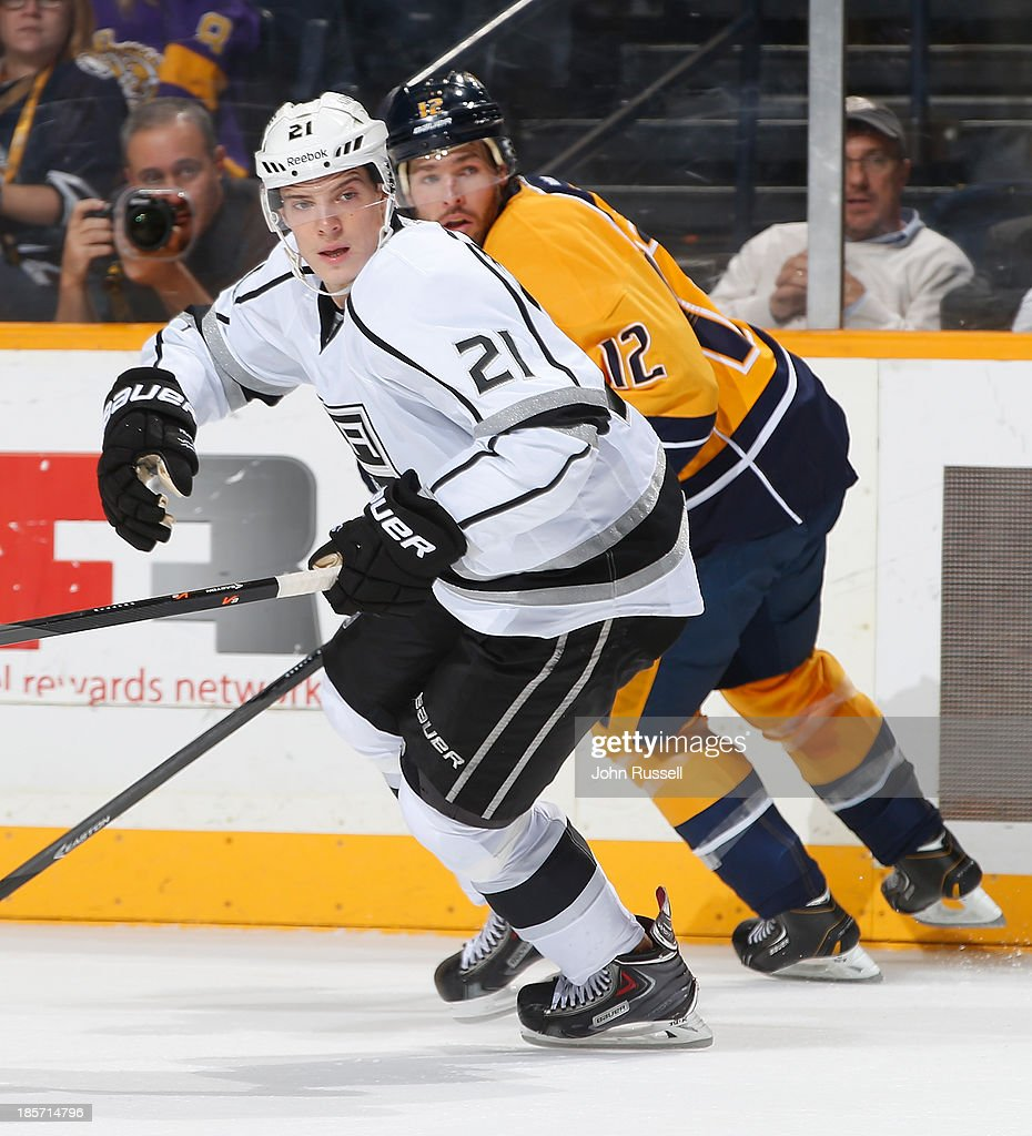 Matt Frattin #21 of the Los Angeles Kings skates against Mike Fisher #12 of the Nashville Predators at Bridgestone Arena on October 17, 2013 in Nashville, Tennessee.