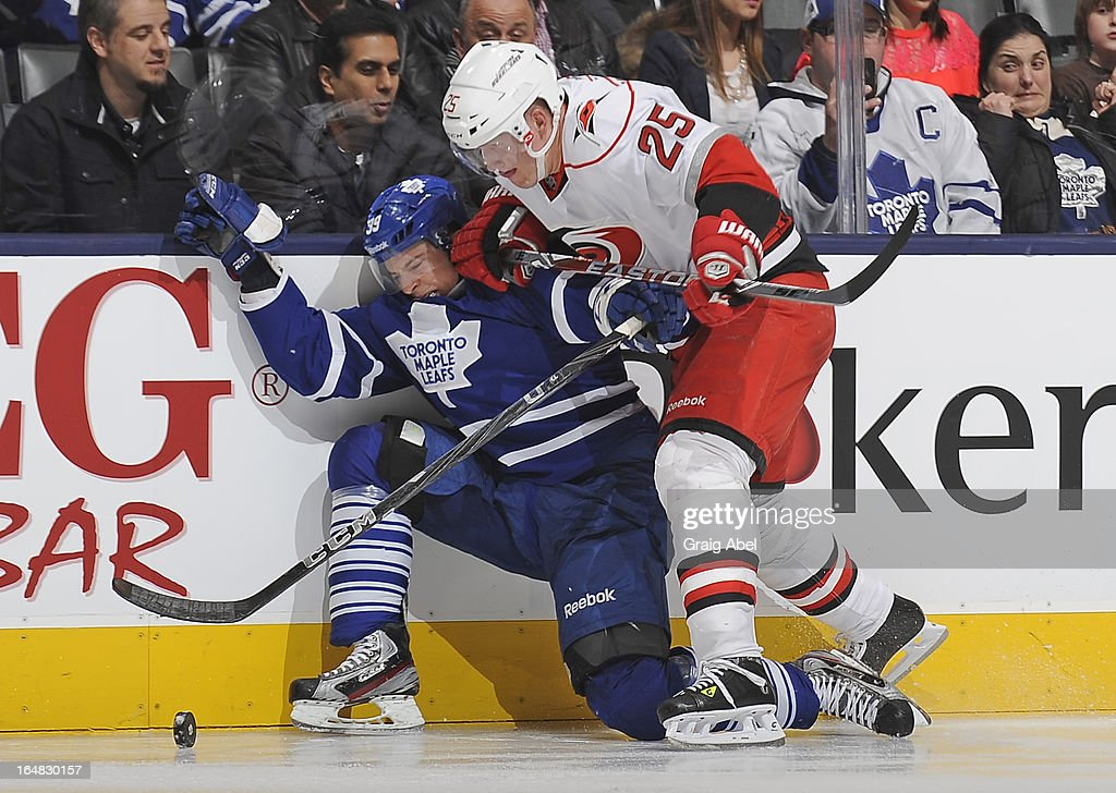 Matt Frattin #39 of the Toronto Maple Leafs battles for the puck with <a gi-track='captionPersonalityLinkClicked' href=/galleries/search?phrase=Joni+Pitkanen&family=editorial&specificpeople=204480 ng-click='$event.stopPropagation()'>Joni Pitkanen</a> #25 of the Carolina Hurricanes during NHL game action March 28, 2013 at the Air Canada Centre in Toronto, Ontario, Canada.