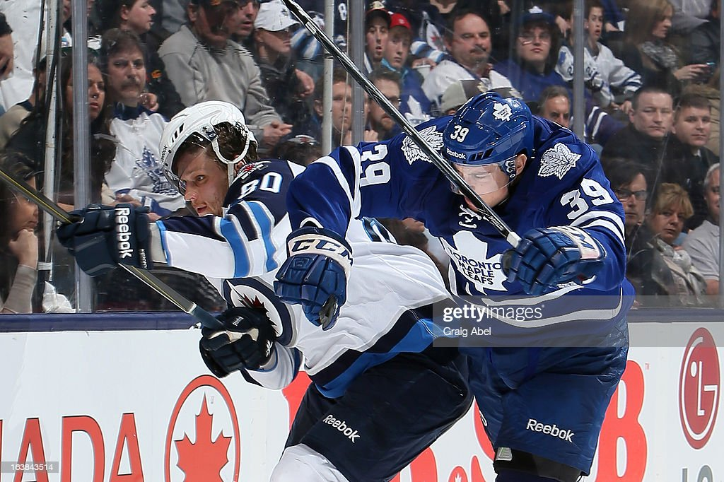 Matt Frattin #39 of the Toronto Maple Leafs checks <a gi-track='captionPersonalityLinkClicked' href=/galleries/search?phrase=Nik+Antropov&family=editorial&specificpeople=202953 ng-click='$event.stopPropagation()'>Nik Antropov</a> #80 of the Winnipeg Jets during NHL game action March 16, 2013 at the Air Canada Centre in Toronto, Ontario, Canada.