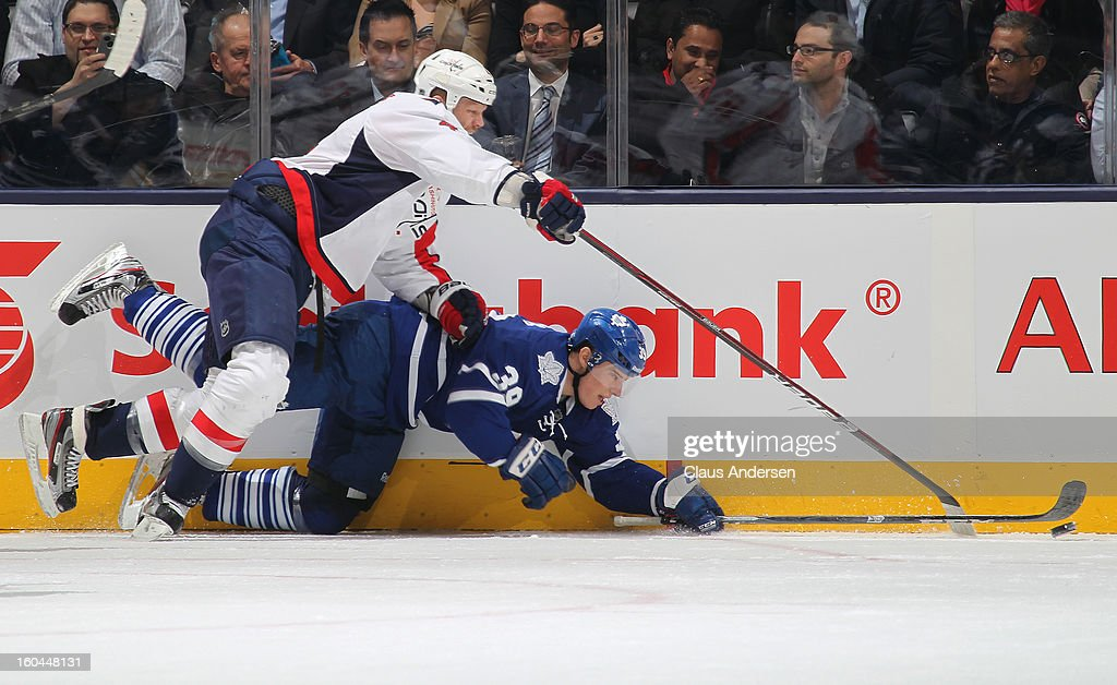 Matt Frattin #39 of the Toronto Maple Leafs is knocked down by <a gi-track='captionPersonalityLinkClicked' href=/galleries/search?phrase=John+Erskine&family=editorial&specificpeople=215268 ng-click='$event.stopPropagation()'>John Erskine</a> #4 of the Washington Capitals while going after a puck in a game on January 31, 2013 at the Air Canada Centre in Toronto, Canada. The Maple Leafs defeated the Capitals 3-2.