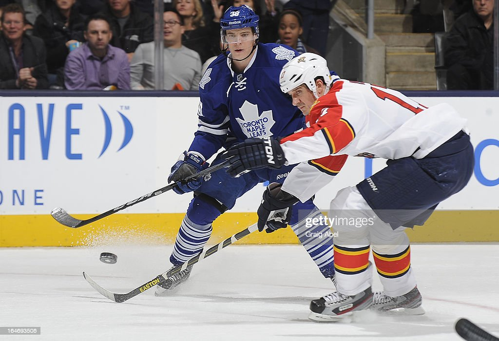Matt Frattin #39 of the Toronto Maple Leafs passes the puck as Filip Kuba #17 of the Florida Panthers defends during NHL game action March 26, 2013 at the Air Canada Centre in Toronto, Ontario, Canada.