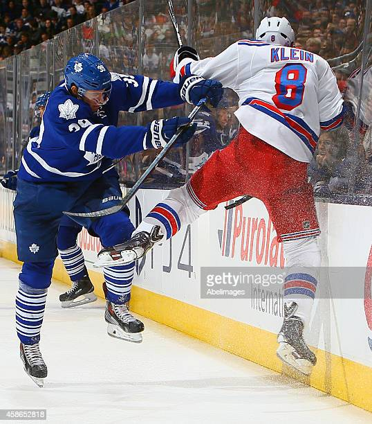 Matt Frattin of the Toronto Maple Leafs runs into Kevin Klein of the New York Rangers during NHL action at the Air Canada Centre November 8 2014 in...