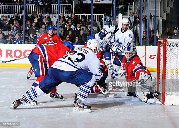 Matt Frattin of the Toronto Marlies is stopped by David Leggio of he Rochester Americans as Nazim Kadri of the Marlies looks on during AHL game...